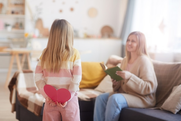 Achteraanzicht portret van schattig meisje met handgemaakte kaart voor moeder terwijl haar verrassen op moederdag in gezellig interieur, kopie ruimte
