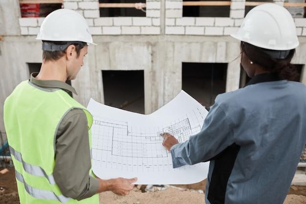 Achteraanzicht portret van twee arbeiders die plattegronden bespreken op de kopieerruimte van de bouwplaats