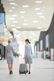Achteraanzicht portret van twee elegante stewardessen weglopen van de camera en chatten op de luchthaven