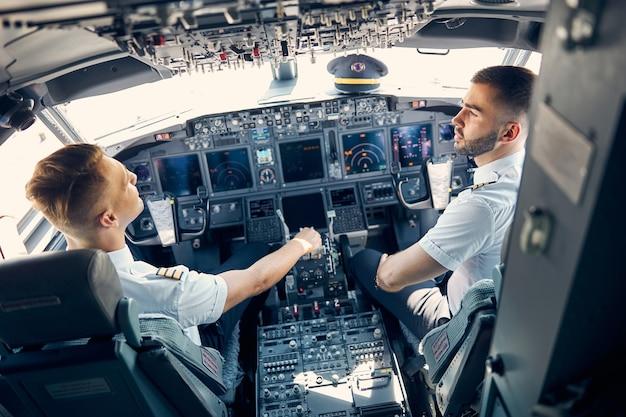 Achteraanzicht portret van twee piloten die het vluchtplan voor hun vlucht bespreken terwijl ze op de stoel in de cabine zitten