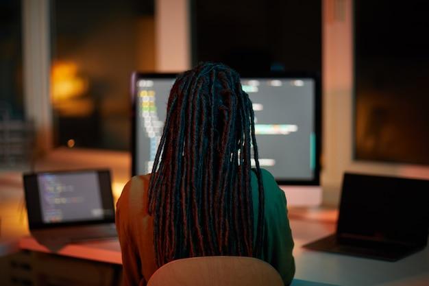 Achteraanzicht portret van vrouwelijke it-ontwikkelaar code schrijven op meerdere computerschermen terwijl u laat in een donkere kantoor, kopie ruimte werkt