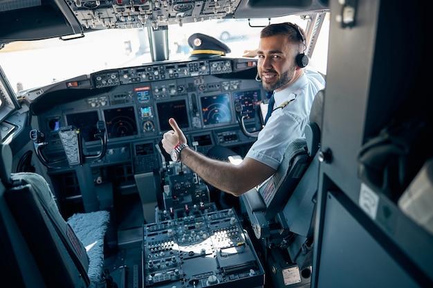 Achteraanzicht portret van zelfverzekerde piloot met koptelefoon zittend op de stoel in de cockpit van een burgervliegtuig