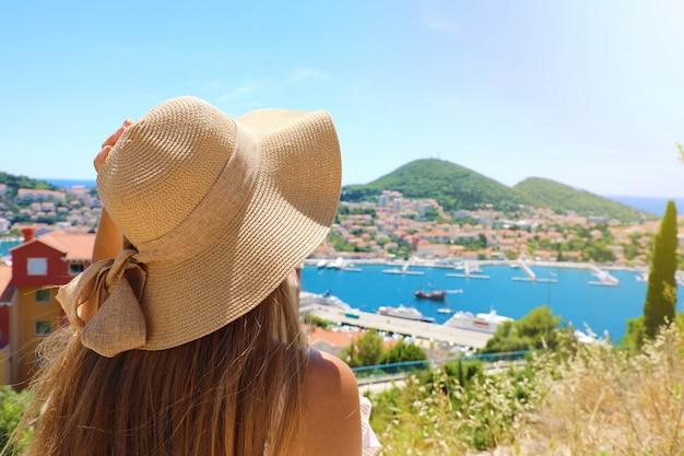 Achteraanzicht reiziger vrouw met hoed kijken naar dubrovnik landschap, kroatië, europa