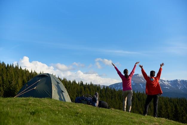 Achteraanzicht schot van twee gelukkige vrouwelijke wandelaars omarmen ochtendzon op de top van een heuvel staan met hun armen gestrekt