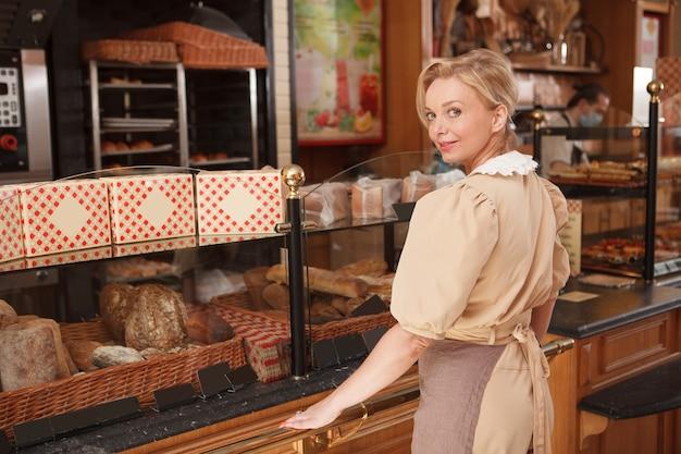 Achteraanzicht shot van een vrolijke volwassen vrouwelijke bakker die geniet van het werken in haar bakkerijwinkel
