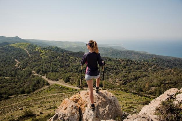 Achteraanzicht sportieve meisje permanent op de rots in korte broek met wandelstokken