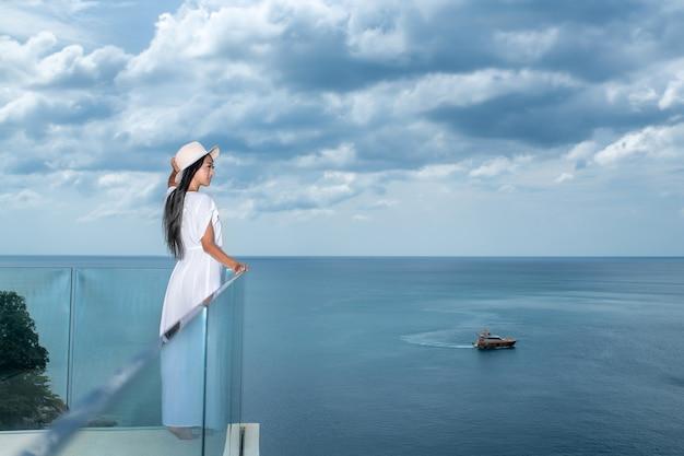 Achteraanzicht staat een prachtige vrouw met lang zwart haar op een transparant terras