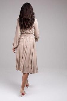 Achteraanzicht stijlvolle brunette meisje in elegantie jurk ga weg geïsoleerd op witte studio achtergrond volledig schot. achteraanzicht modieus meisje met lang mooi haar dat gaat ontsnappen