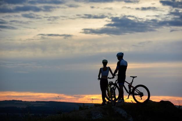 Achteraanzicht twee jongeren met mountainbikes staan op de top van de klif met een prachtig landschap bij zonsondergang