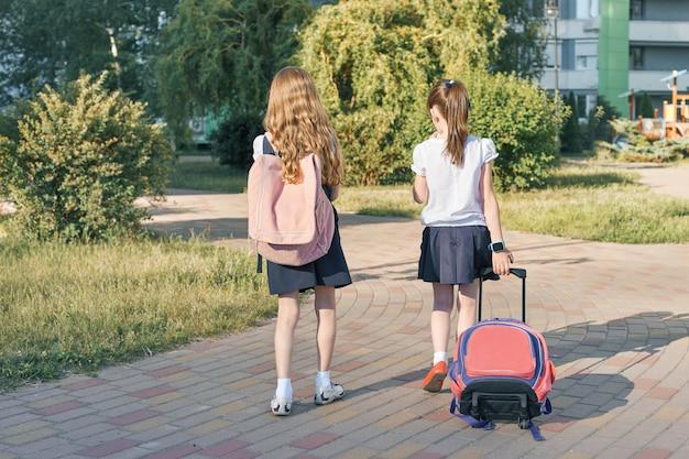 Achteraanzicht, twee kleine meisjes schoolmeisjes gaan naar school met rugzakken