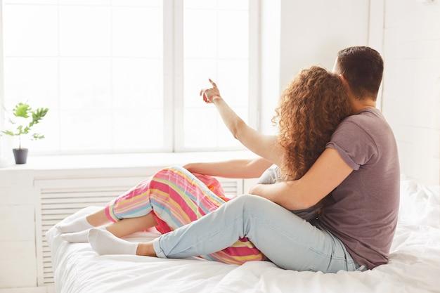 Achteraanzicht van aanhankelijk paar omhelst hartstochtelijk, zit op comfortabel bed en kijk in raam, geniet van daglicht, vrouwtje wijst naar iets met vinger. getrouwde vrouw en man in de slaapkamer