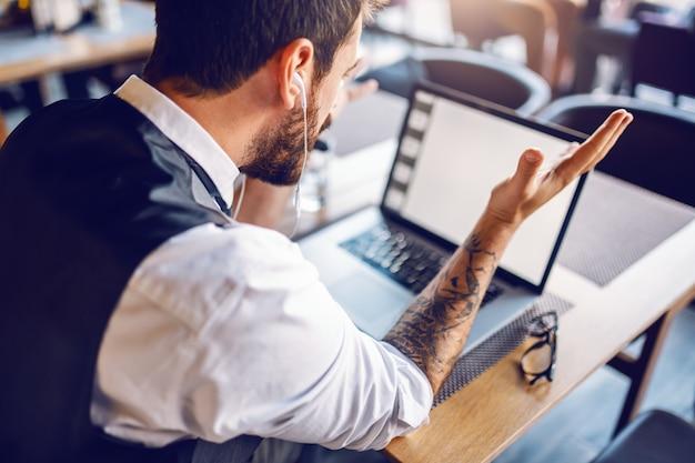 Achteraanzicht van aantrekkelijke blanke bebaarde zakenman zitten in cafe en debat met collega via internet.