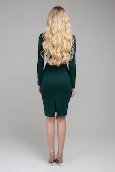 Achteraanzicht van aantrekkelijke blonde vrouw met lang krullend blond haar in avondjurk geïsoleerd op witte studio achtergrond. achteraanzicht mode meisje met slank lichaam staande in elegante kleding