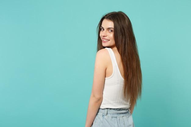 Achteraanzicht van aantrekkelijke schattige jonge vrouw in lichte casual kleding terugkijkend geïsoleerd op blauwe turquoise muur achtergrond in studio. mensen oprechte emoties, lifestyle concept. bespotten kopie ruimte.