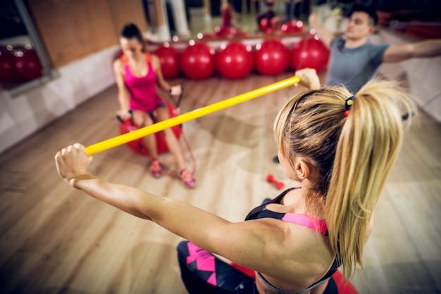 Achteraanzicht van aantrekkelijke vorm blonde fitness vrouw met paardenstaart training met een gele balk voor groepsgenoot in de sportschool.