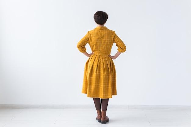 Achteraanzicht van aantrekkelijke vrouw in een gele jurk die zich voordeed op witte kamer met copyspace