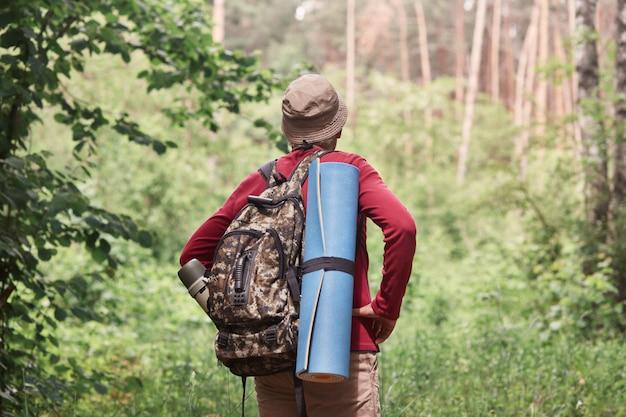 Achteraanzicht van actieve backpacker op zoek naar een uitweg in het bos, met slaapmat en donkere rugzak met thermoskan aan zijn rug, genietend van een actieve vakantie, blijf bij de levensstijl. reizen concept.