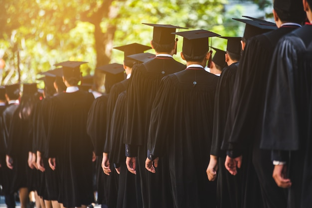 Achteraanzicht van afgestudeerden nemen deel aan de diploma-uitreiking op de universiteit. onderwijs afstuderen in universitaire thema concept.