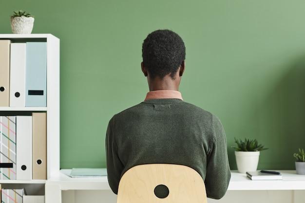 Achteraanzicht van afrikaanse man zit aan het bureau werken of studeren