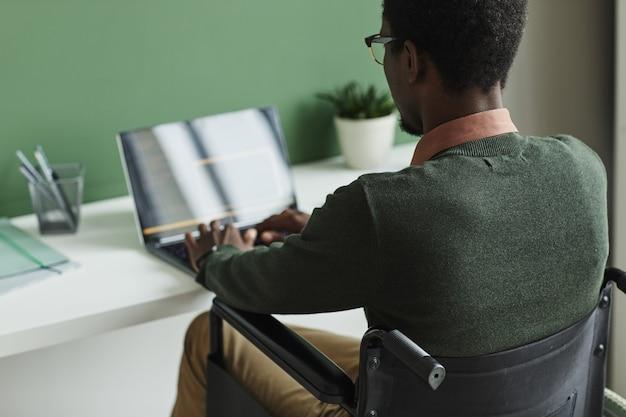 Achteraanzicht van afrikaanse man zittend op rolstoel te typen op laptop aan de tafel op kantoor