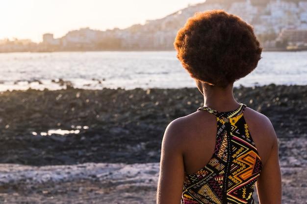 Achteraanzicht van afro-etnische vrouw met traditionele kleding en afrikaanse kapsel kijkend naar de oceaan en zonsondergang - zwarte vrouwelijke mensen genieten alleen van reizen en vrijetijdsbesteding in de buitenlucht