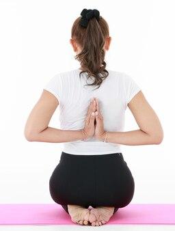 Achteraanzicht van anonieme vrouw die handen achter de rug omklemt terwijl ze op de mat knielt en mediteert.