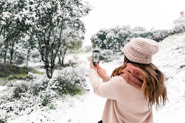 Achteraanzicht van anonieme vrouw in warme bovenkleding permanent in bos en het nemen van foto van schilderachtige besneeuwde landschap tijdens het gebruik van smartphone
