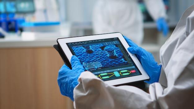 Achteraanzicht van arts in beschermingspak die virusevolutie analyseert die op digitale tablet kijkt. team van wetenschappers die vaccinontwikkeling uitvoeren met behulp van hightech voor onderzoek naar behandeling tegen covid19