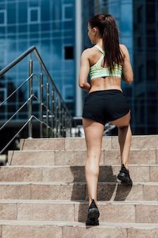 Achteraanzicht van atleet draait op trappen