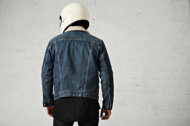 Achteraanzicht van atletische fietser dragen club denim shearling jas en helm, geïsoleerd op wit