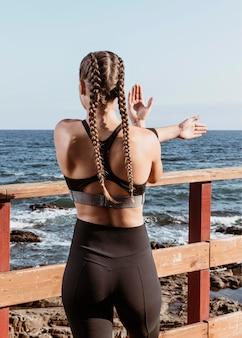 Achteraanzicht van atletische vrouw buiten aan het strand die zich uitstrekt terwijl je het uitzicht bewondert