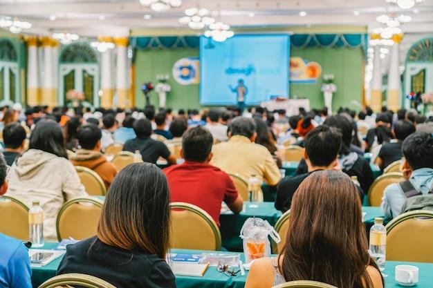 Achteraanzicht van audience die de sprekers beluistert, presenteert de dia op het podium in de conferentie