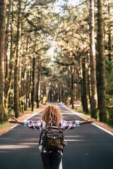 Achteraanzicht van avonturiersvrouw die op de weg in het midden van het bos loopt
