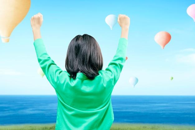Achteraanzicht van aziatisch meisje dat kleurrijke luchtballon bekijkt die met blauwe hemelachtergrond vliegt