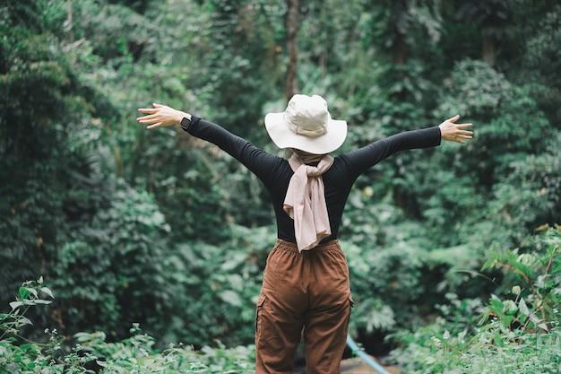 Achteraanzicht van aziatische moslim wandelaar vrouw bruine hijab staande voor het tropische woud met haar handen omhoog.