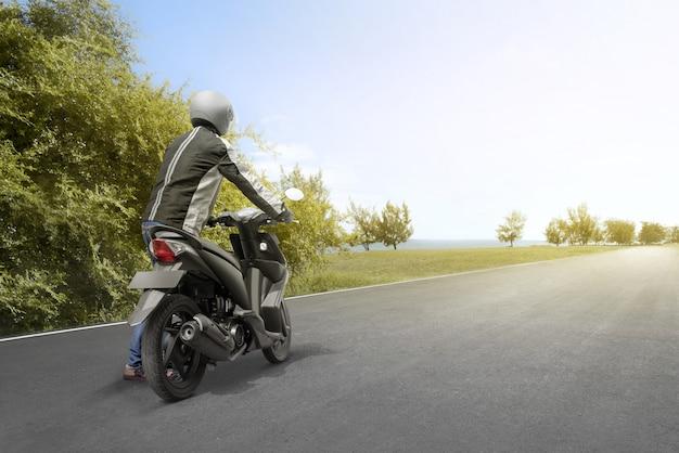 Achteraanzicht van aziatische motorfiets taxi man duwt zijn motorfiets