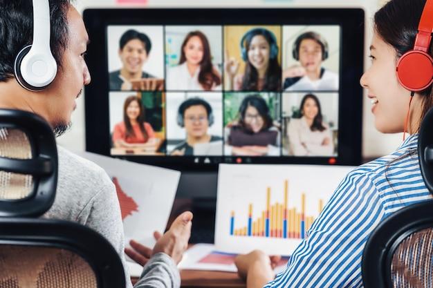 Achteraanzicht van aziatische partner die werkt en online vergadert via videoconferentie met collega