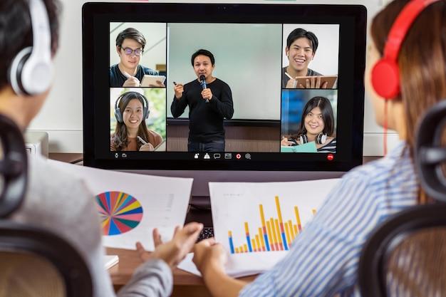 Achteraanzicht van aziatische partner die werkt en online vergadert via videoconferentie met spreker