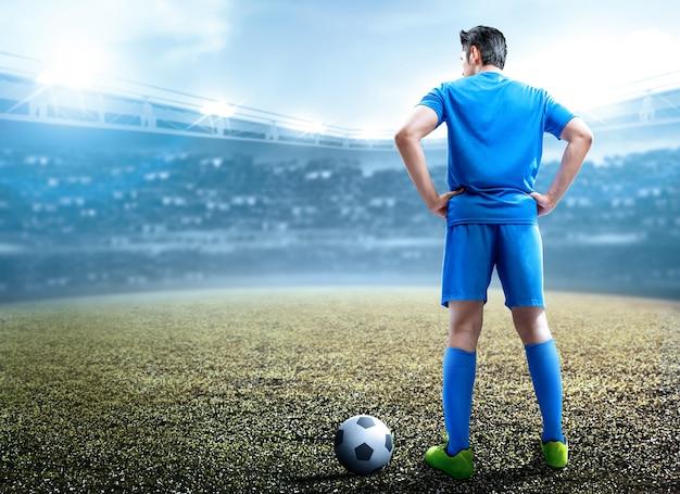 Achteraanzicht van aziatische voetballer man die met de bal