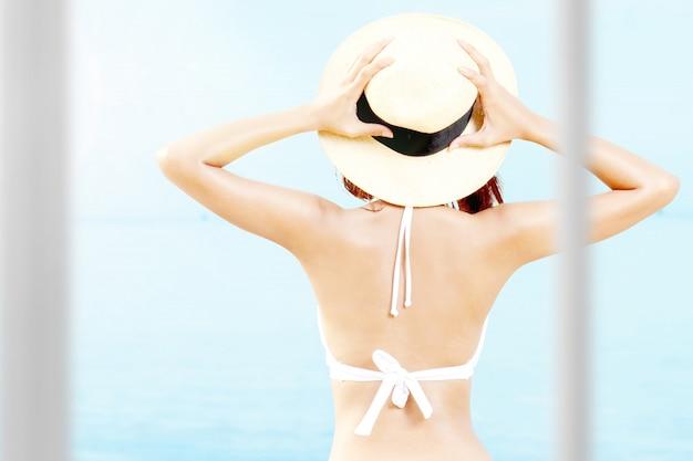 Achteraanzicht van aziatische vrouw met bikini en hoed ontspannen op het strand
