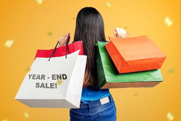 Achteraanzicht van aziatische vrouw met boodschappentassen na het winkelen op eindejaarsuitverkoop. gelukkig nieuwjaar 2021