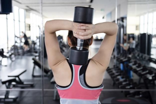 Achteraanzicht van aziatische vrouw oefenen haar triceps met dumbell