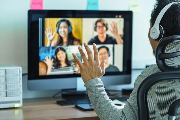 Achteraanzicht van aziatische zaken man hallo zeggen met teamwerk collega in videoconferentie
