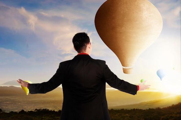 Achteraanzicht van aziatische zakenman die kleurrijke luchtballon bekijkt die met de achtergrond van de zonsonderganghemel vliegt