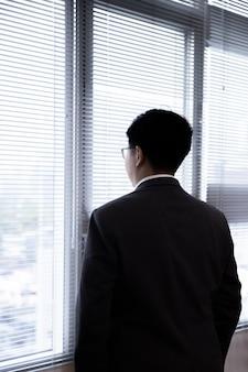 Achteraanzicht van aziatische zakenman in een pak op zoek via loket met lege copyspace