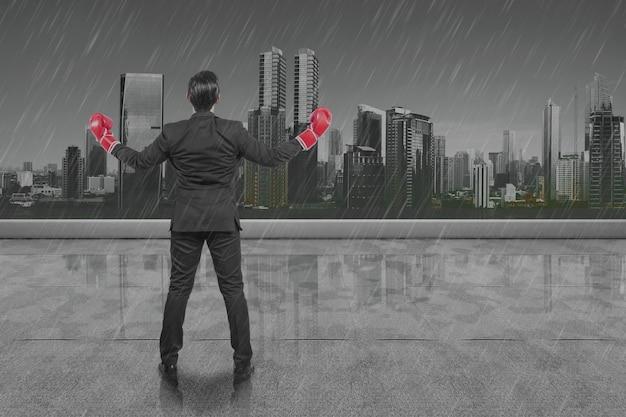 Achteraanzicht van aziatische zakenman met rode bokshandschoenen met regenachtige achtergrond