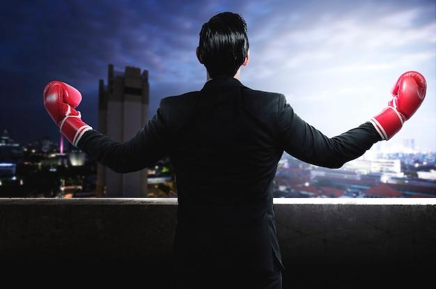 Achteraanzicht van aziatische zakenman met rode bokshandschoenen met stadsgezichten achtergrond