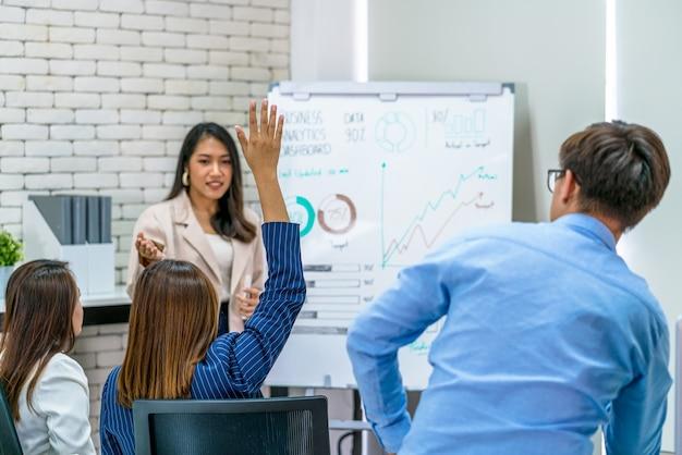Achteraanzicht van aziatische zakenvrouw die hand opsteekt om vragen te stellen aan de spreker tijdens een ontmoeting