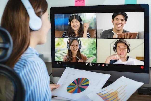 Achteraanzicht van aziatische zakenvrouw die werkt en online vergadert via videoconferentie met collega