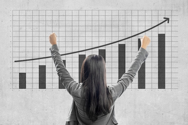 Achteraanzicht van aziatische zakenvrouw kijken naar toegenomen zakelijke financiën grafiek met muur achtergrond